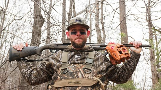 Brandon Snyder poses with two tools representing his dual trades, MLB and Hunting. A Benelli Super Black Eagle and Rawlings glove.