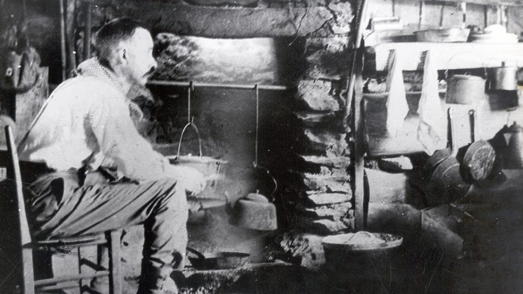 Horace Kephart sits in his cabin and enjoys a fire.